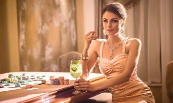 Nainen juomassa drinkkiä pelipöydän vieressä
